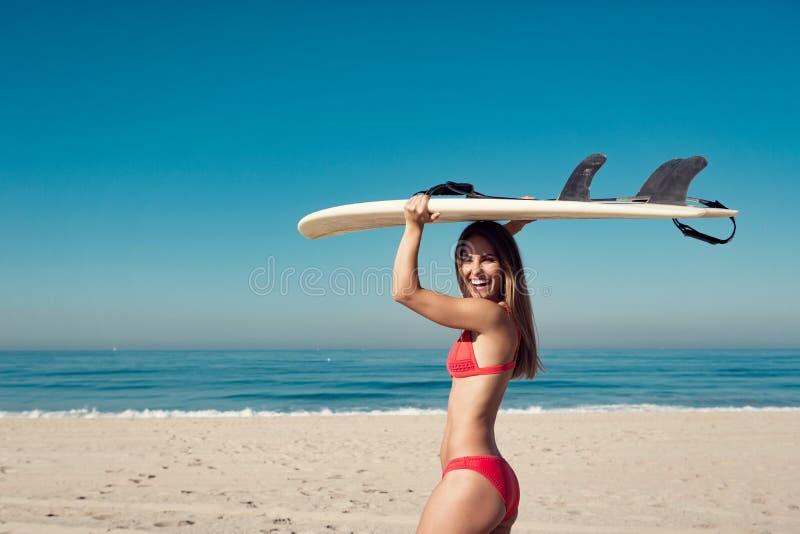 运载冲浪板的少妇在海滩 库存照片