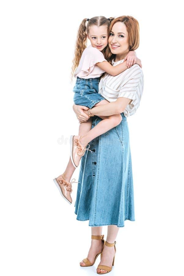 运载可爱的矮小的女儿和微笑对照相机的愉快的母亲 免版税库存照片