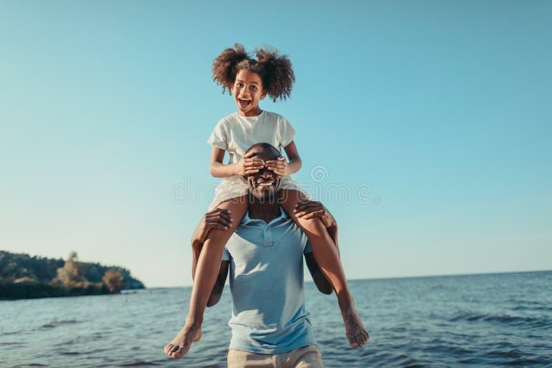 运载可爱的矮小的女儿的微笑的非裔美国人的父亲 免版税库存照片