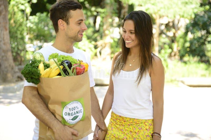 运载回收纸袋有机菜ans的愉快的夫妇充分结果实。 库存图片