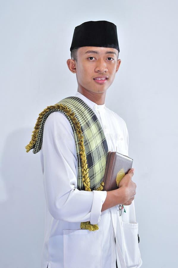运载圣洁古兰经的年轻穆斯林画象在斋月kareem 免版税库存照片