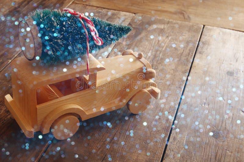 运载圣诞树的木汽车 闪烁覆盖物 免版税库存照片