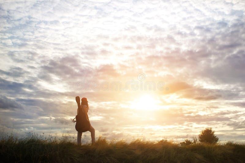 运载在她的肩膀,乡下路的妇女一把吉他 免版税库存图片