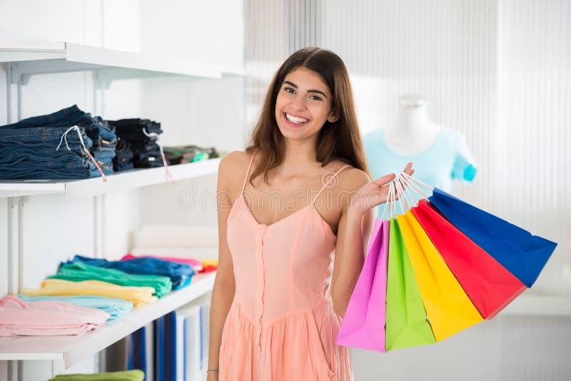 运载在服装店的微笑的妇女五颜六色的购物袋 图库摄影