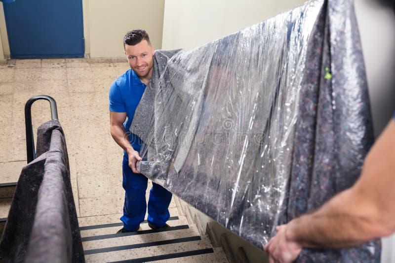 运载在楼梯的两名搬家工人家具 库存照片