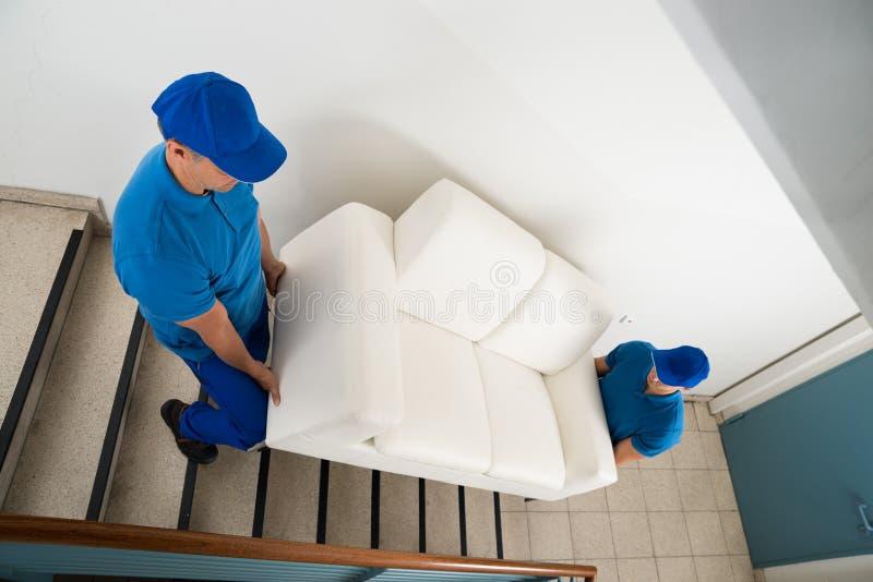运载在楼梯的两名搬家工人沙发 库存照片