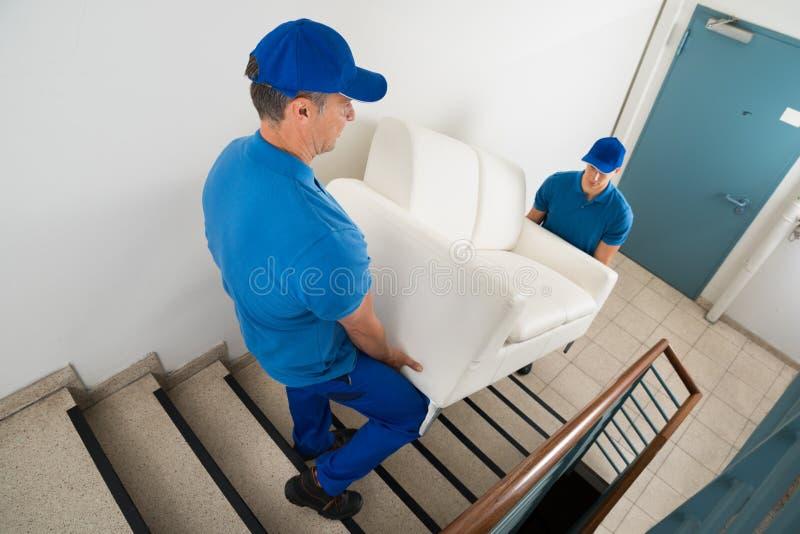 运载在楼梯的两名搬家工人沙发 库存图片