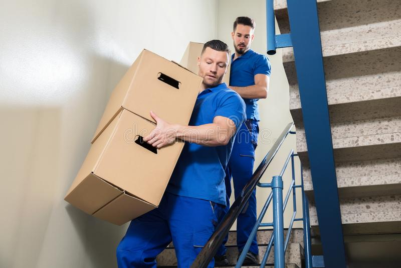 运载在楼梯的两名搬家工人纸板箱 库存照片