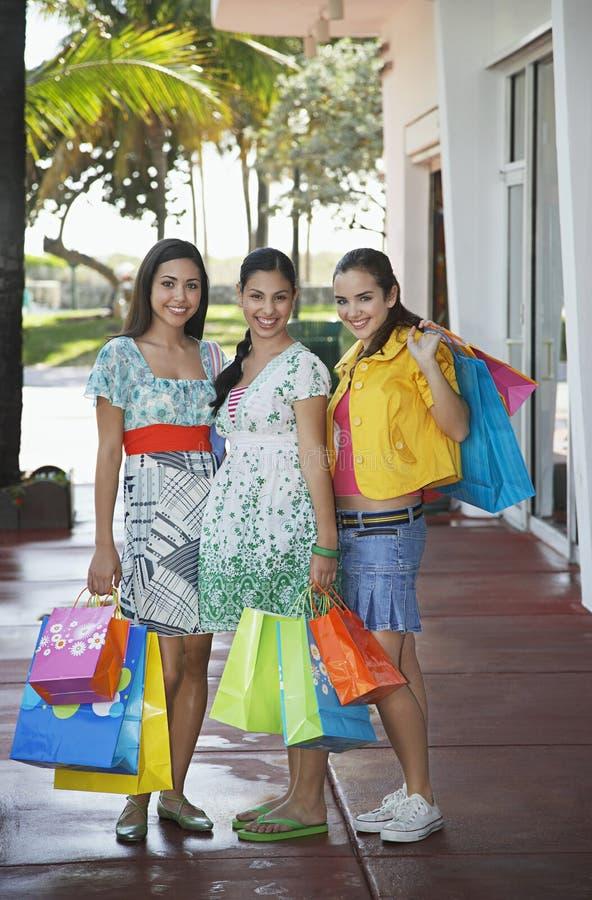 运载在边路的十几岁的女孩购物袋 免版税库存图片