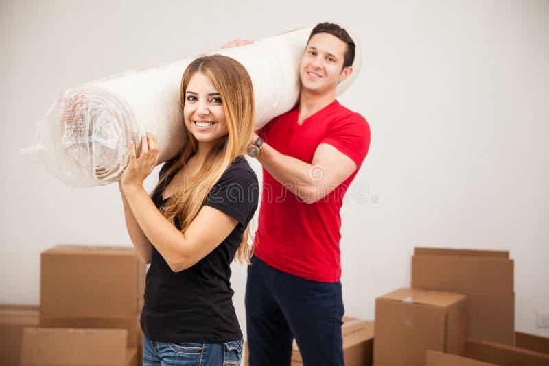运载地毯的逗人喜爱的夫妇 免版税库存照片