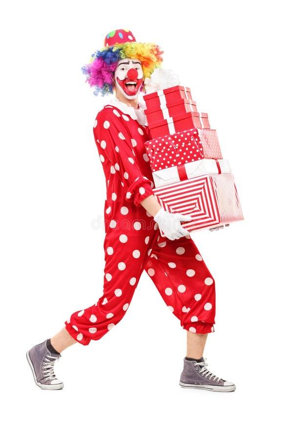 运载堆礼物的男性小丑 免版税库存图片