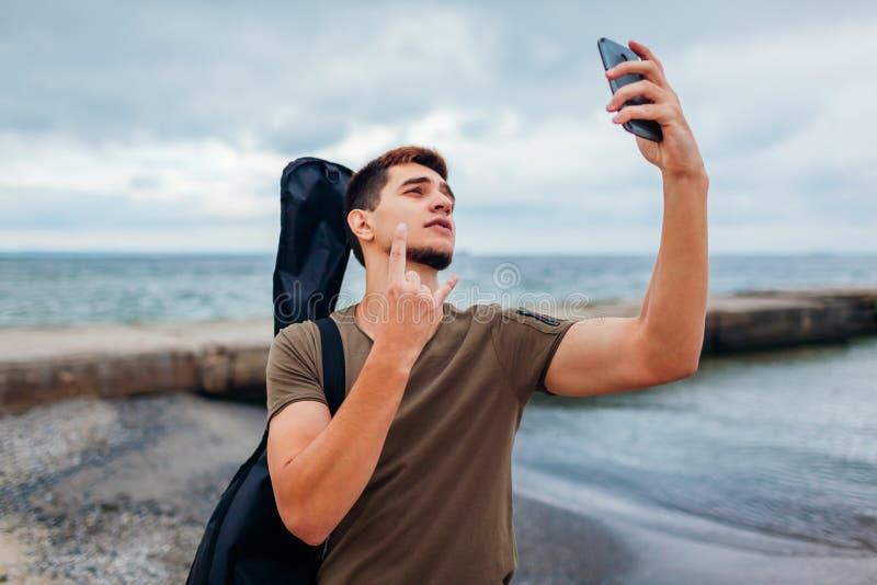 运载声学吉他和采取selfie的年轻人使用在多云海滩的电话 人显示rockstar标志 免版税库存图片