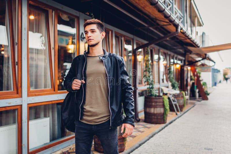 运载声学吉他的年轻人,万一,当走在城市街道上由咖啡馆时 音乐学院的行家学生 免版税库存图片
