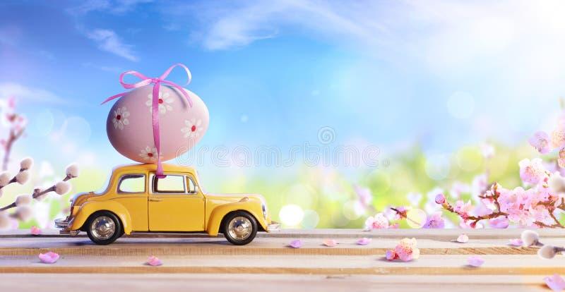 运载复活节彩蛋的被扭屈的和无法认出的汽车 图库摄影