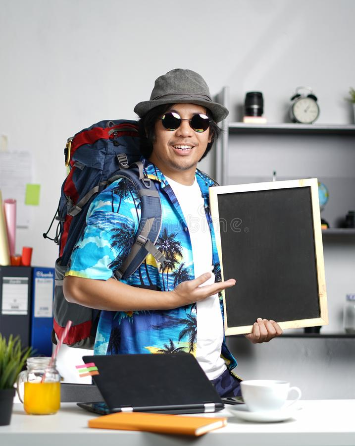 运载大背包和拿着黑板a的时髦的年轻人 免版税库存图片