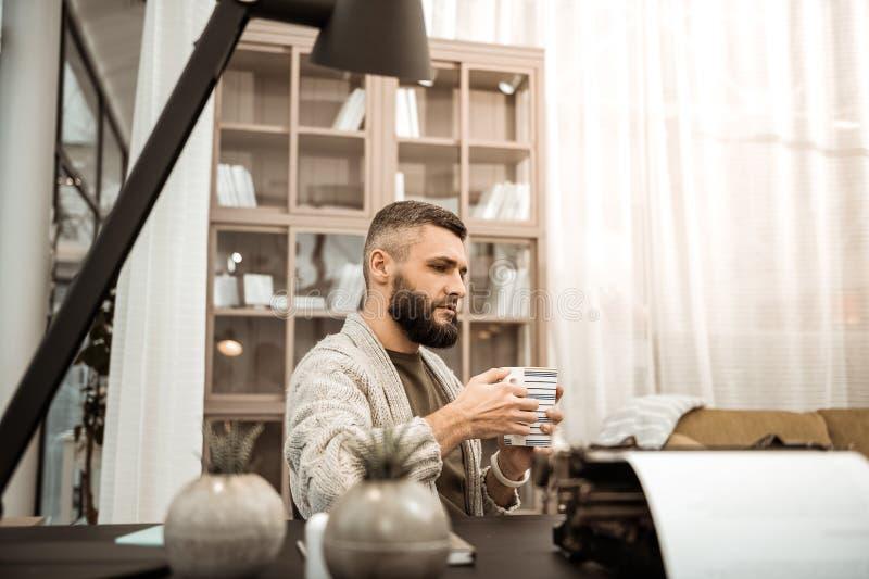 运载大茶的被编织的羊毛衫的严肃的体贴的人 免版税图库摄影