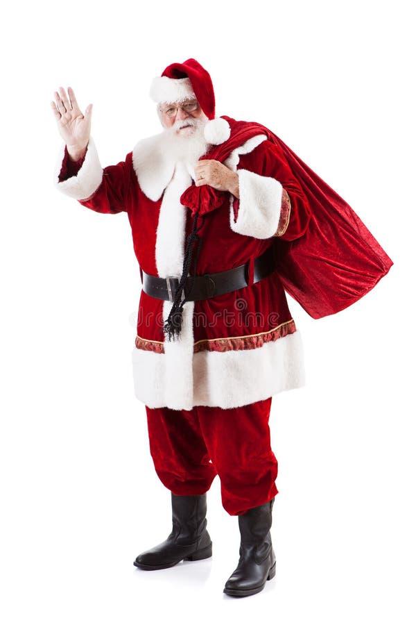 运载大袋圣诞礼物和挥动的圣诞老人项目 库存图片