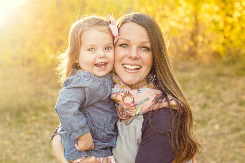 运载她微笑的逗人喜爱的女儿的年轻母亲户外 免版税图库摄影