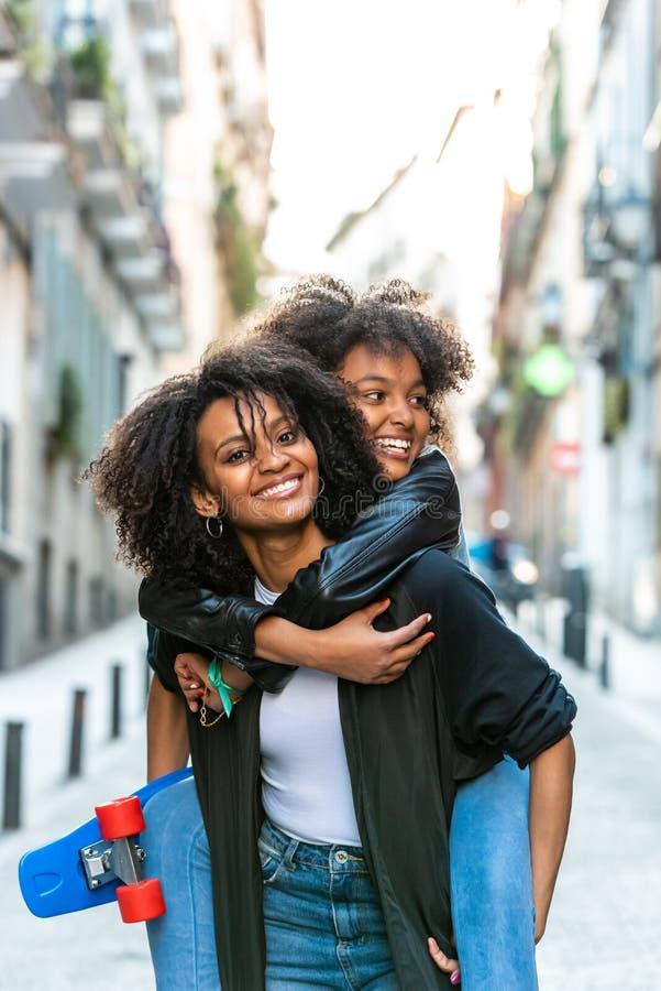 运载她的后面的母亲女儿 免版税库存照片