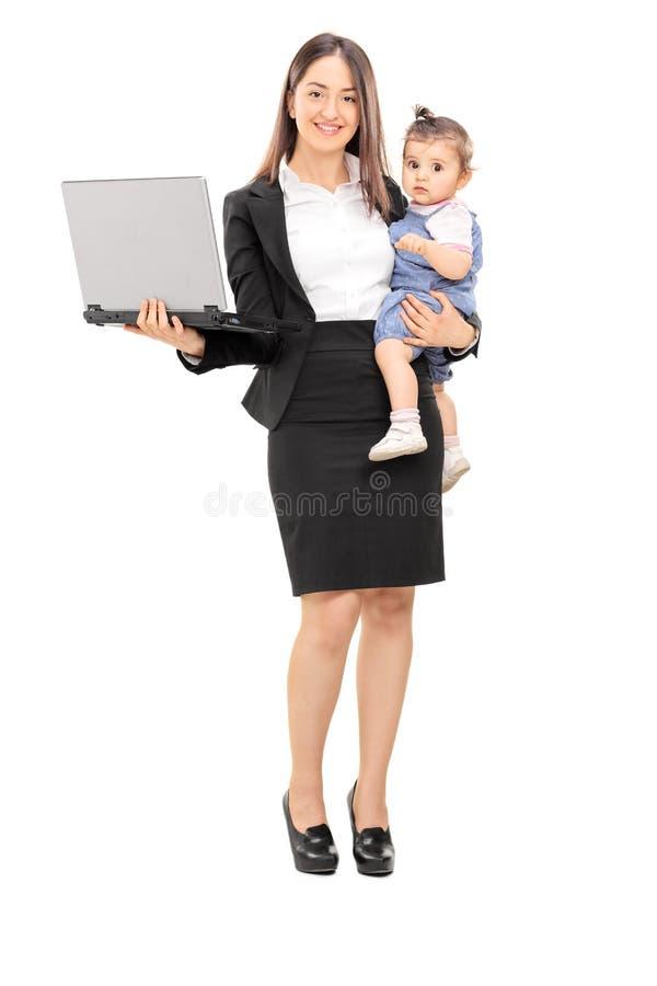 运载她的女儿和拿着膝上型计算机的女实业家 免版税库存图片
