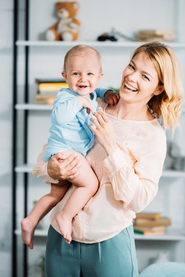 运载她的小孩的笑的母亲 免版税图库摄影