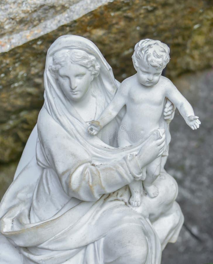 运载婴孩的圣母玛丽亚的白色石雕象 库存照片