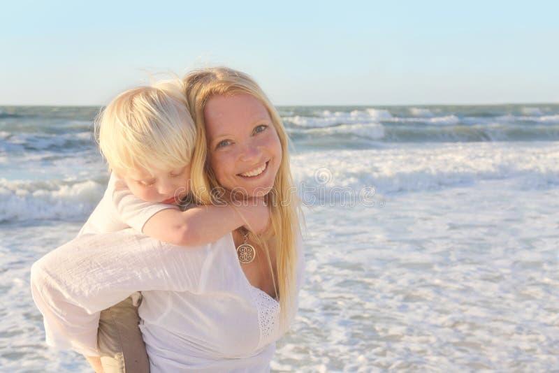 运载幼儿肩扛的母亲通过海洋水 免版税库存照片