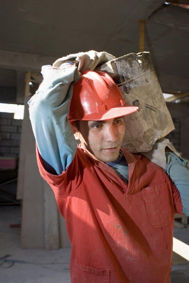 运载建筑材料垂直工作者 免版税库存图片