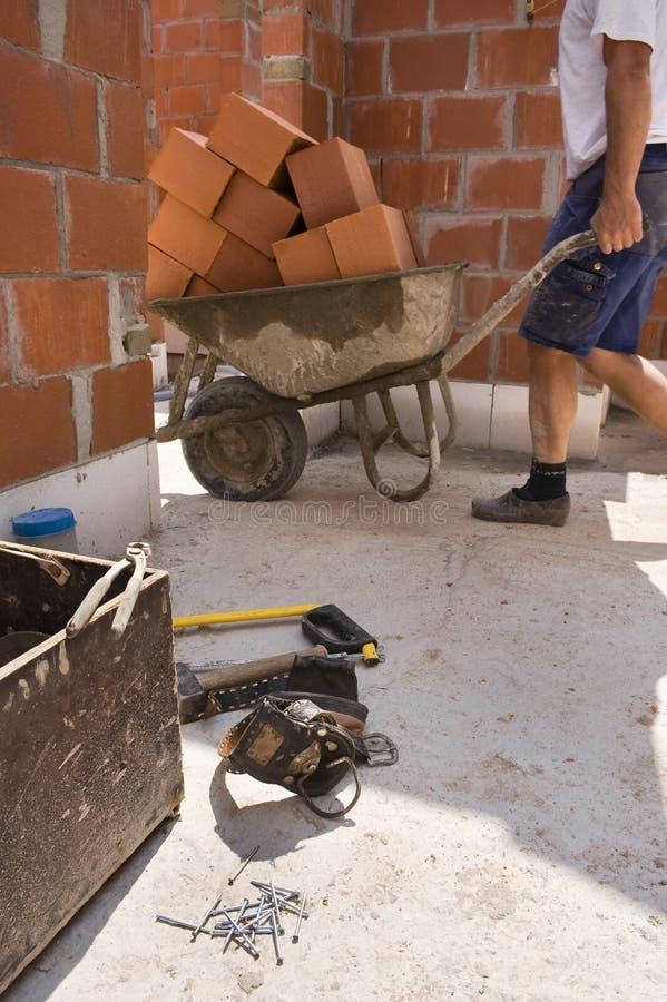 运载建筑的建造者在独轮车之下 库存照片