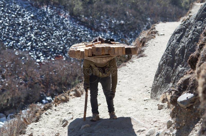 运载担子的尼泊尔搬运工在尼泊尔喜马拉雅山 免版税图库摄影