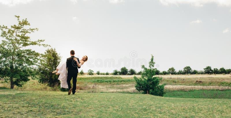 运载新娘的新郎在公园 免版税库存照片