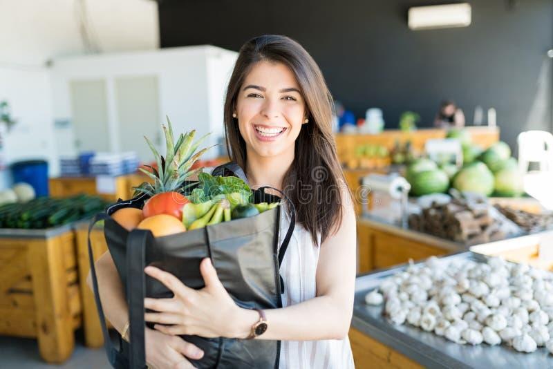 运载新鲜的健康食品的微笑的妇女在商店 库存图片