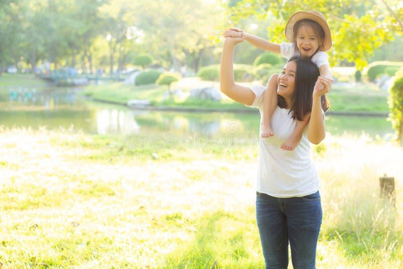运载有微笑的,儿童乘驾的美丽的年轻亚裔母亲一点女儿在妈妈的脖子充满幸福和快乐 库存照片
