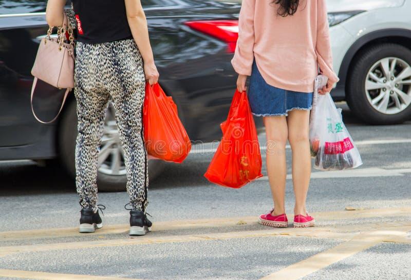 运载杂货以各种各样的用过即弃的塑料购物带来的妇女 免版税库存图片