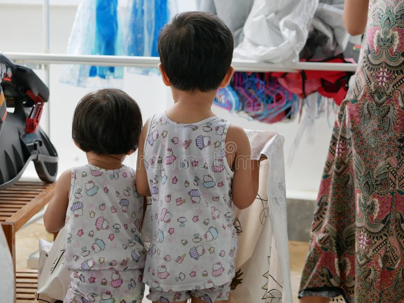 运载桌布的两个小亚裔女婴他们的母亲垂悬它和得到它干燥在洗涤以后为 免版税库存照片