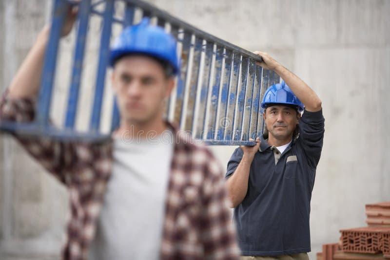 运载梯子的建筑工人 免版税库存图片