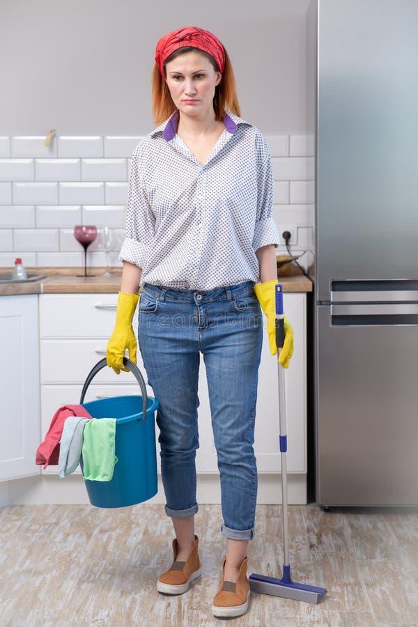 运载清洗的桶笤帚和拖把的洗涤的橡胶手套的年轻可爱的被注重的服务妇女被挫败和劳累过度 免版税库存图片