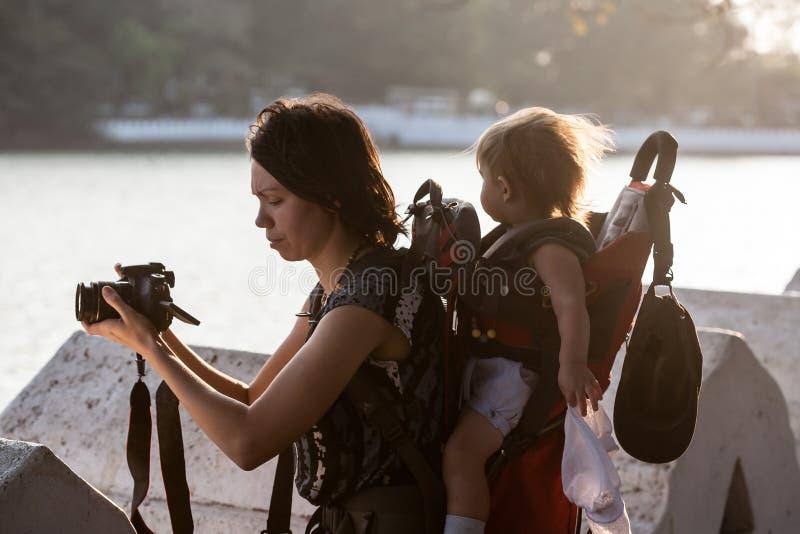 运载的背包的女婴享受旅行冒险的, 免版税库存图片