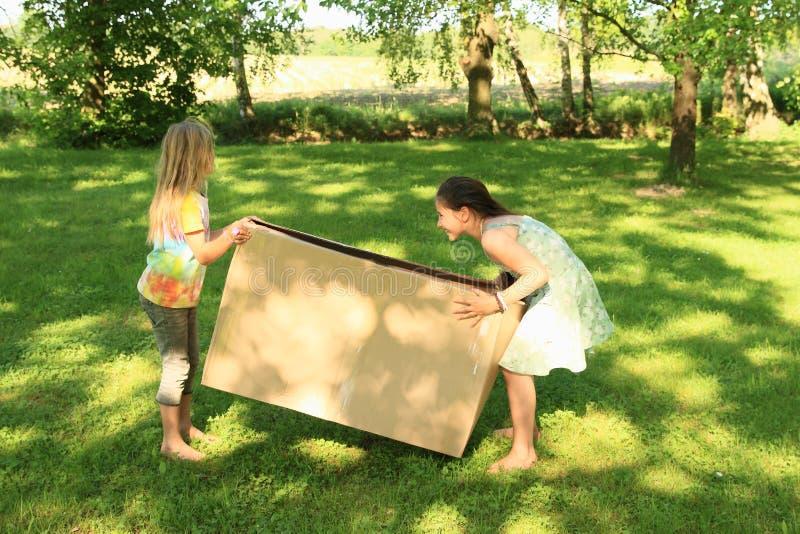 运载箱子的孩子 免版税库存照片
