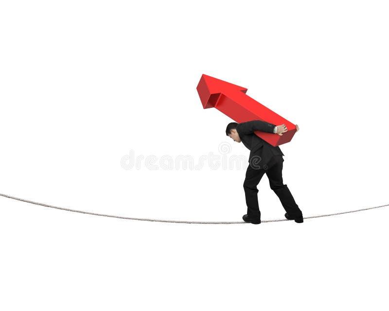 运载红色箭头标志的商人平衡在绳索 免版税库存照片