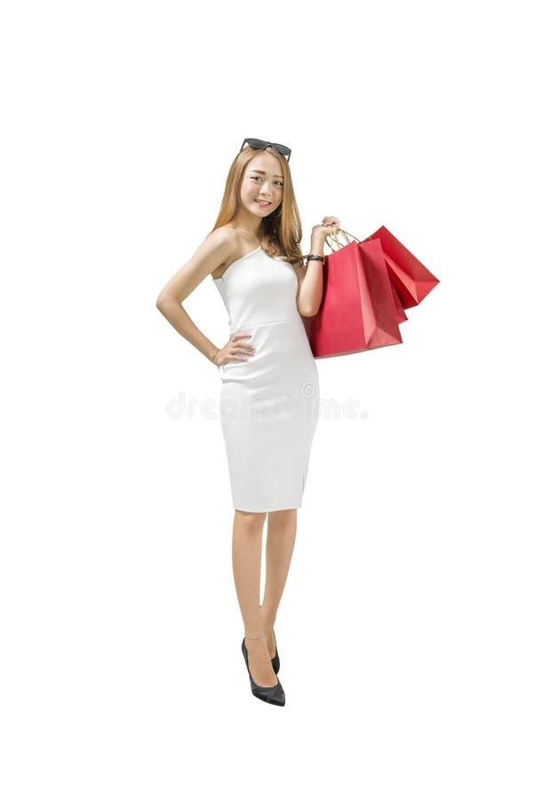 运载红色购物袋站立的微笑的亚裔豪华妇女 图库摄影