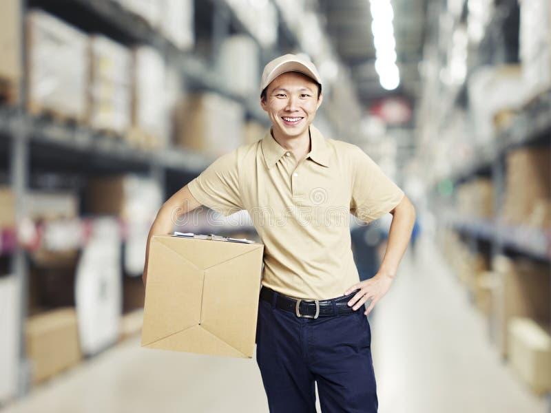 运载纸盒箱子的一名年轻仓库工作者的画象 免版税图库摄影