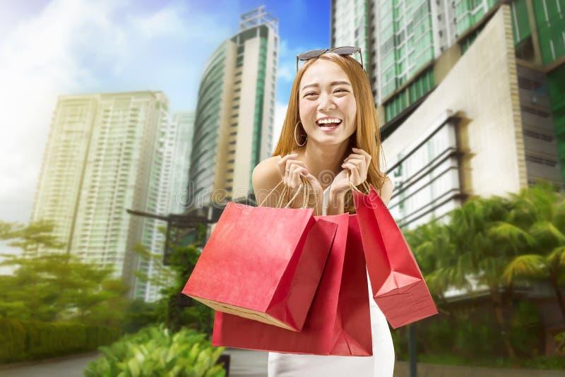 运载色的纸袋的愉快的亚裔女孩在购物以后在m 免版税库存照片