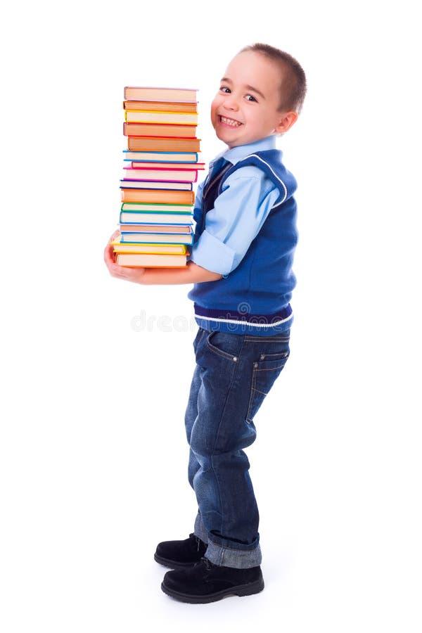运载被堆积的书的小男孩 免版税库存照片