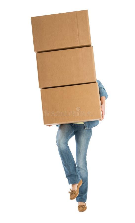 运载被堆积的纸板箱的妇女,当站立在一条腿时 库存图片