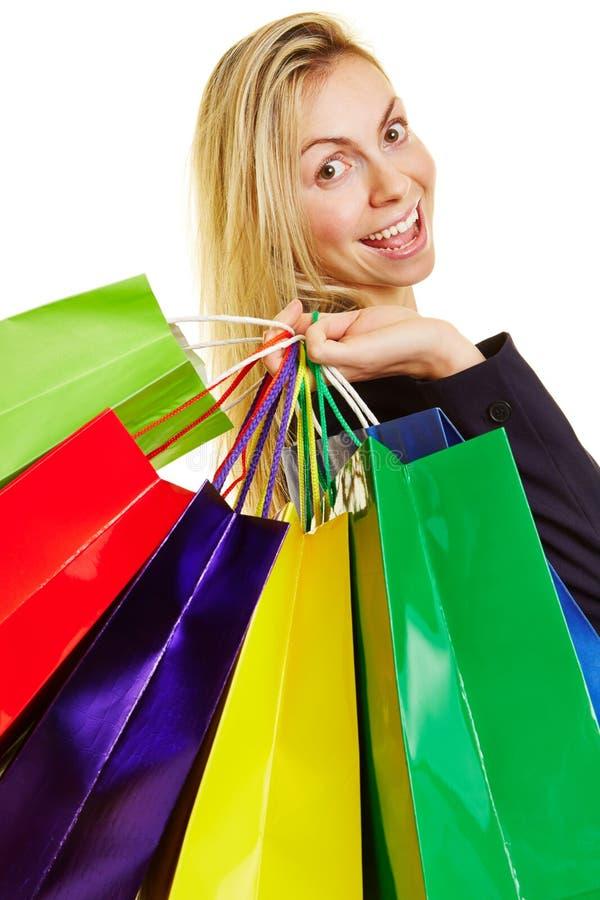运载许多购物袋的愉快的妇女 免版税图库摄影