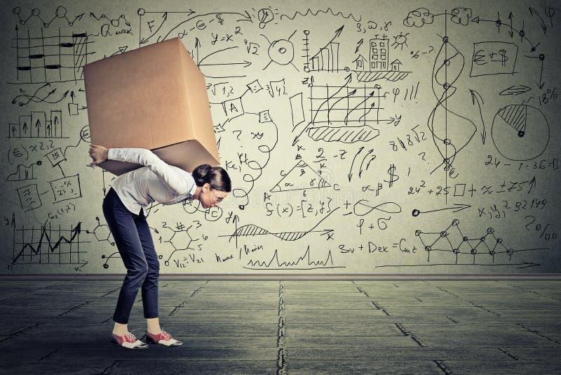 运载重的箱子的妇女走沿灰色墙壁 免版税库存照片
