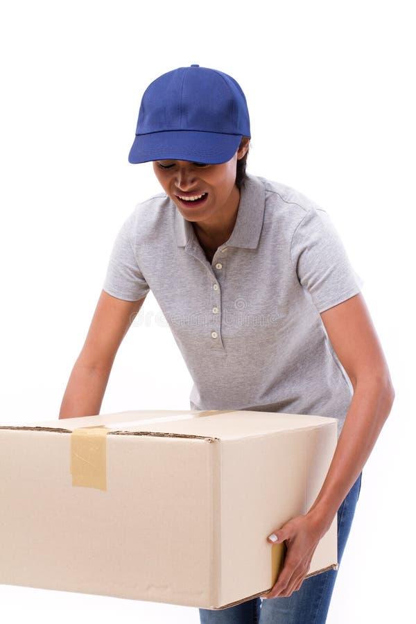 运载重的纸盒箱子的女性交付职员 库存图片