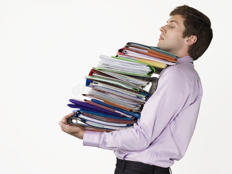 运载重的黏合剂的年轻男性办公室工作者 免版税库存照片