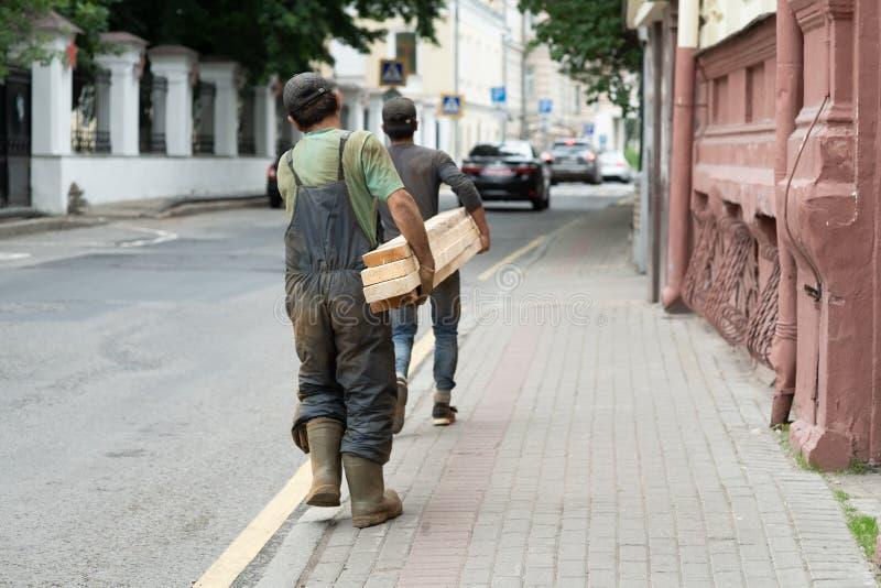 运载长的木板运动的材料的成熟工作员背面图画象在工厂车间 免版税库存照片